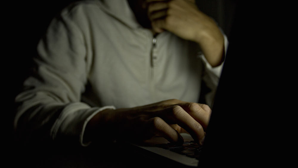 Anonymous male on a laptop at night